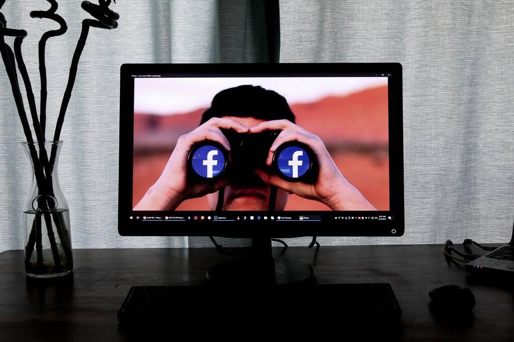 Ein TV mit einem Mann, der ein Fernglas hält auf dem die Logos von Facerbook zu sehen sind, steht sionnbildlich für die Marktrelevanz von Facebook in den sozialen Medien