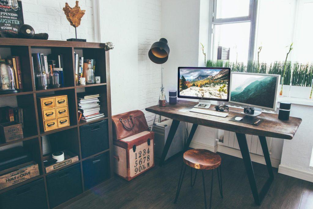 Moderner Arbeitsplatz mit höhenverstellbarem Schreibtisch und zwei Monitoren